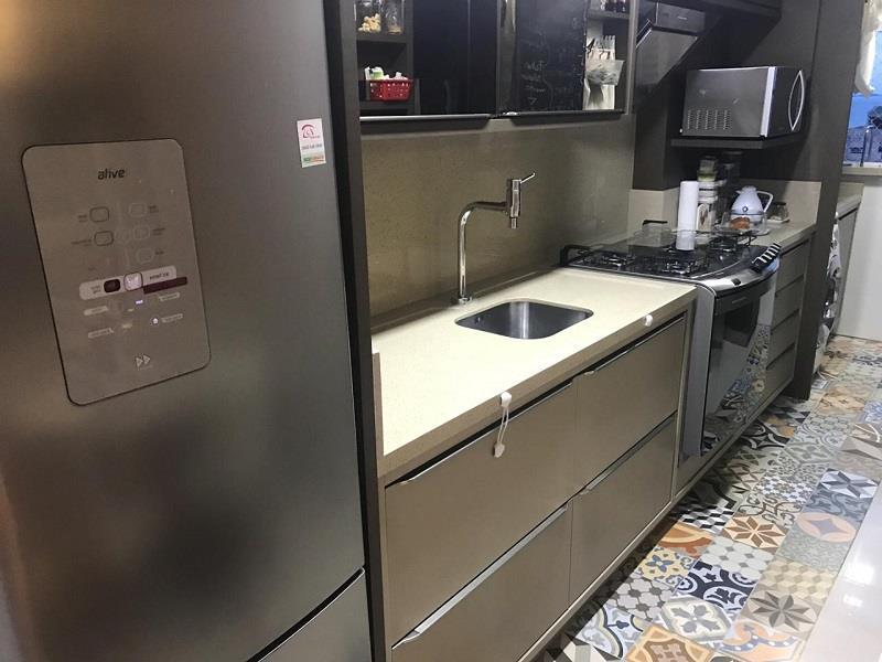 Cozinha com armários planejados, geladeira, fogão e forno com microondas