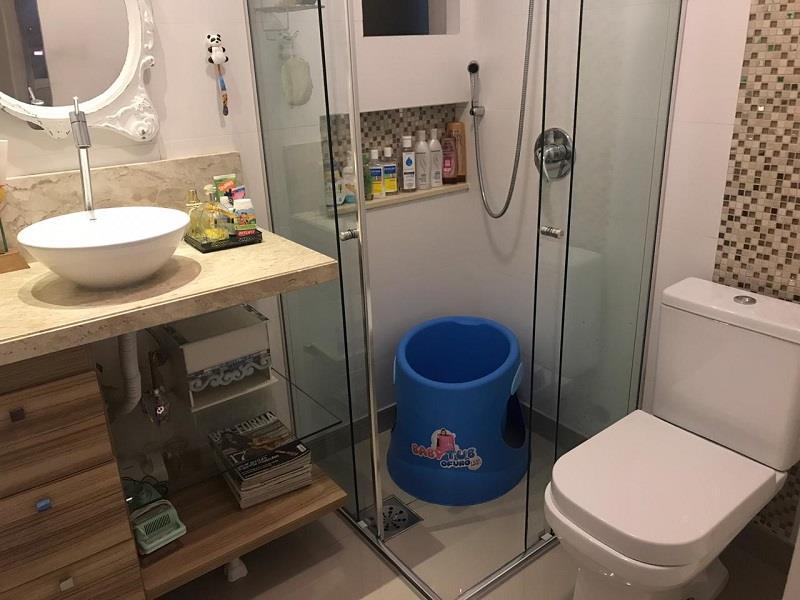 Banheiro Social com armário, espelho e box em vidro.
