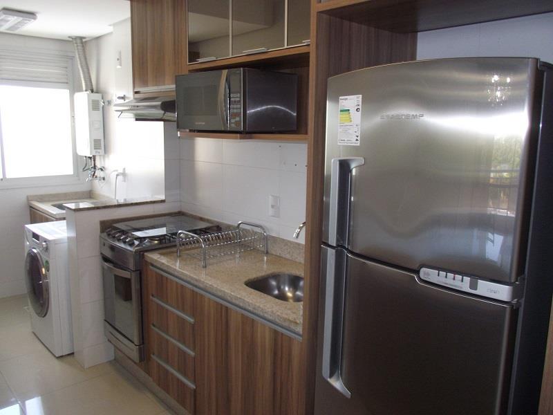 Cozinha com geladeira, armários, fogão e microondas