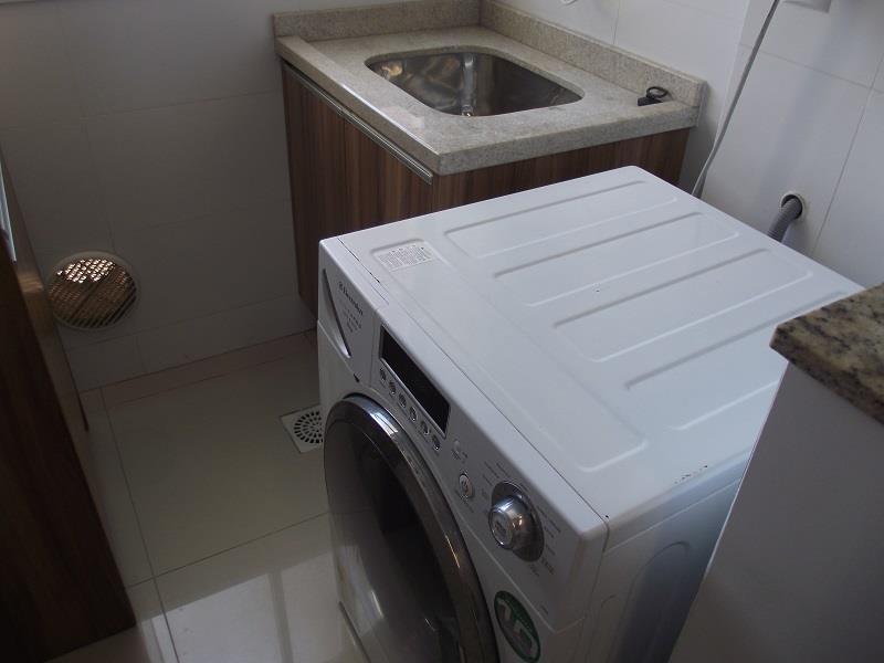 Área de serviço com armário, tanque e máquina de lavar roupas lava e seca.