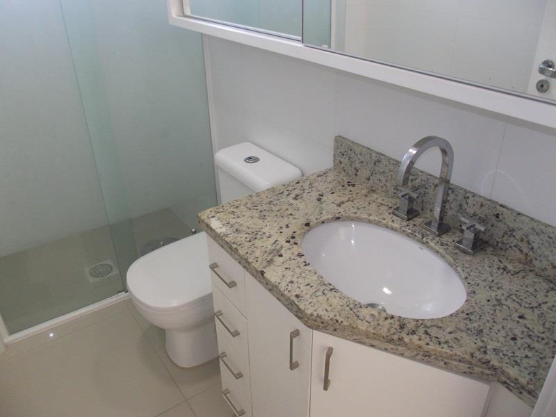 Banheiro social com box em vidro, espelho e armários