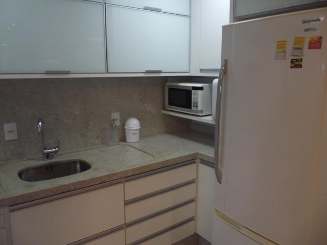 Cozinha com armários planejados, fogão, microondas, geladeira e depurador de água.