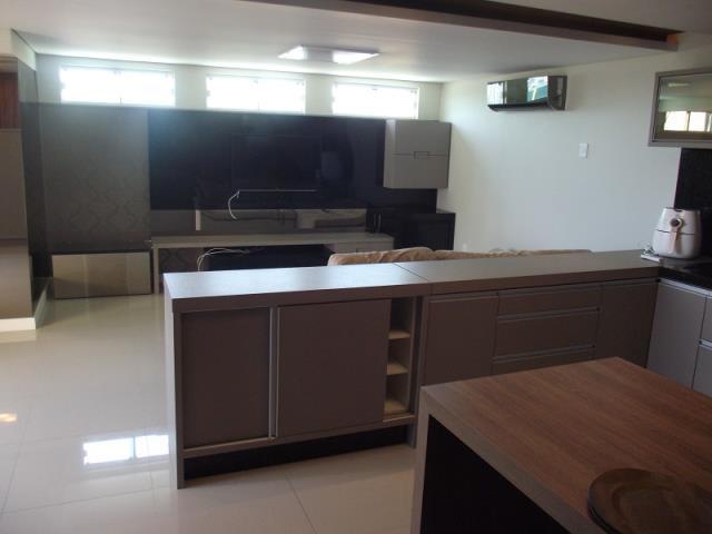 Sala de TV com espaço com churrasqueira e terraço.