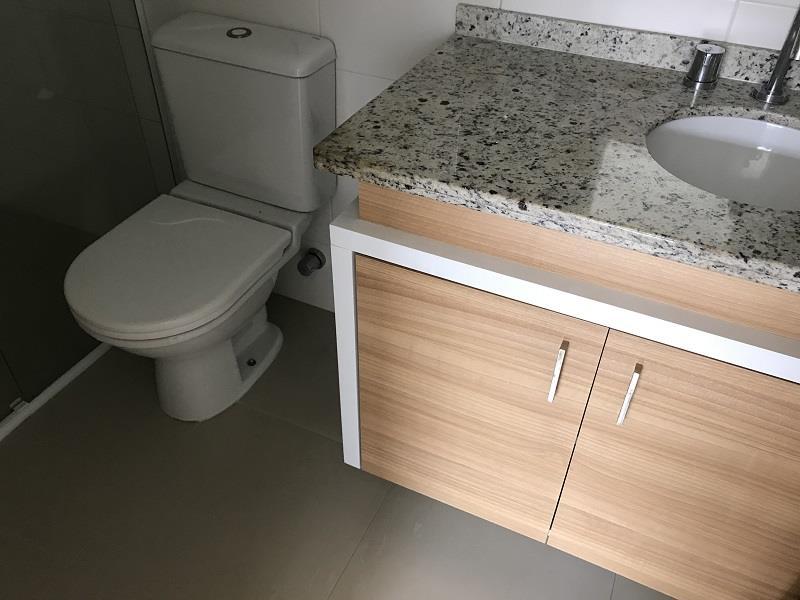 Banheiro Suíte com armários, espelho e box em vidro.