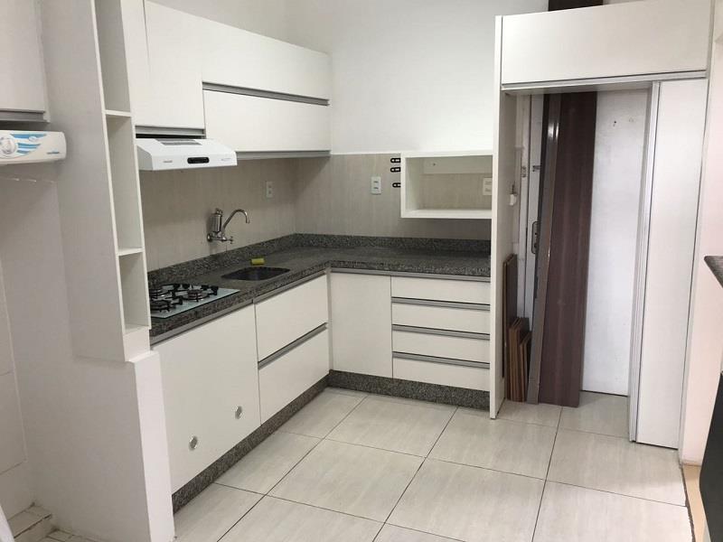 Cozinha com armários, fogão e coiffa