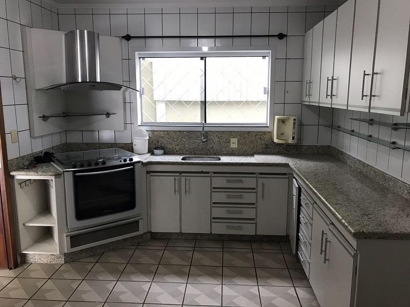 Cozinha com armários planejados com fogão e coiffa.