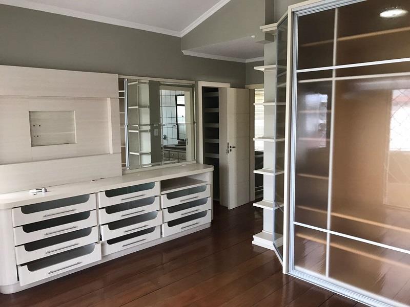 Quarto suíte com armários planejados e painel com sacada