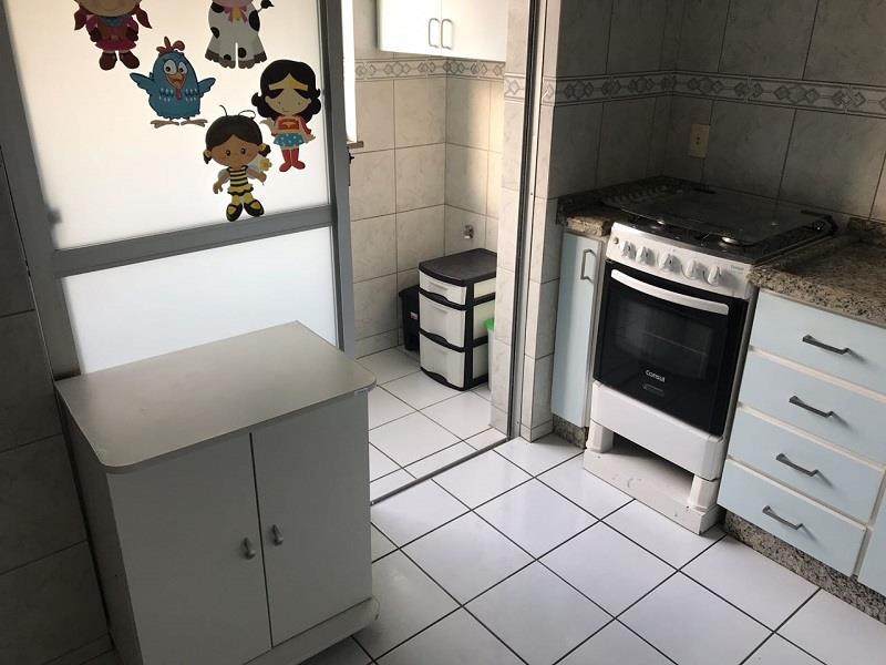 Cozinha com armários, fogão e geladeira
