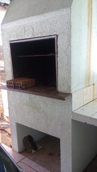 Garagem com churrasqueira, área de serviço e banheiro.