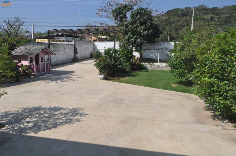 Pátio com área verde, canil e várias plantas.